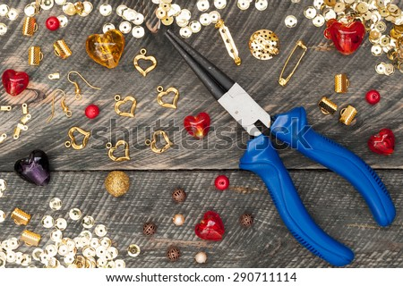Tools for handmade jewelry. Beads, plier, glass hearts and accessories to create hand made jewelry on old wooden background. Top view