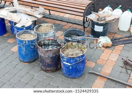 Tools for repairing the sidewalk, a bucket of sand and rubble on the city street. Road repair with building materials. repair construction work