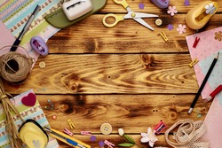 Tools for scrapbooking on the wooden background. Copy space in the middle.
