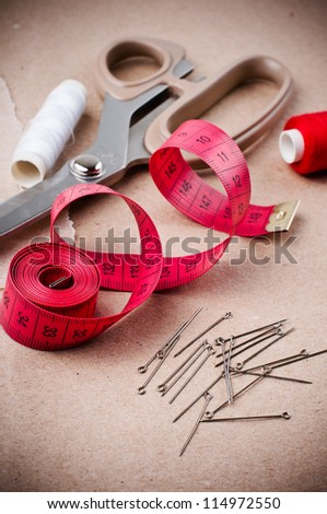 Tools for sewing and handmade: thread, scissors, pins on brown paper.