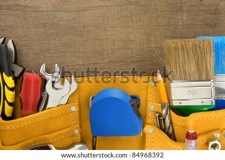 tools in belt on wooden texture