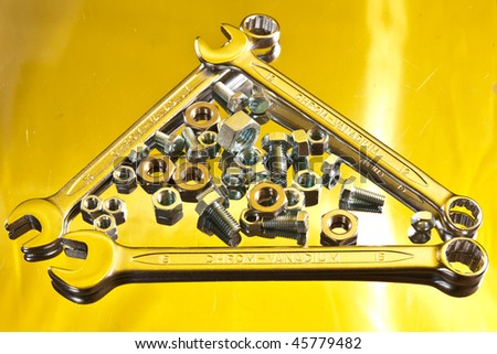 tools series: steel bolt and wrench on reflectife metal surface - stock photo