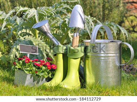tools, watering can and gardening boots in the garden