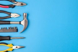 Tools worker, hammer, screwdriver, pliers on a blue background, top view