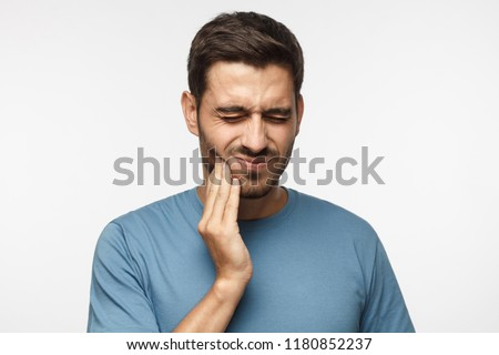 Tooth ache concept. Indoor shot of young male feeling pain, holding his cheek with hand, suffering from bad toothache, looking at camera with painful expression