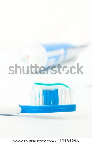 Tooth brush next to a tube of toothpaste against white background