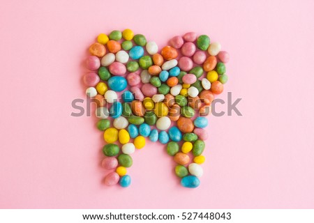 Tooth of sweets scattered on a pink background