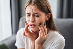 Toothache. Girl suffering from tooth pain and touching cheek while sitting on couch at home. Dental problem concept. Stock photo