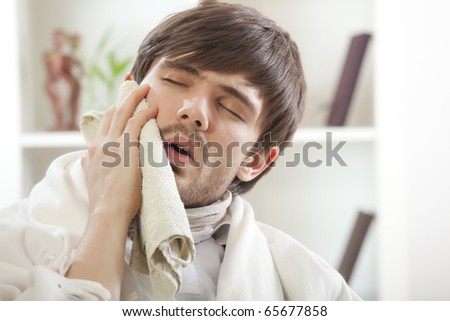 toothache - sick man covering with towel his cheek