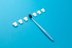 Toothbrush and teeth on blue background. Prevention and care of the oral cavity.