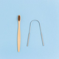 Toothbrush and tongue scraper on a blue background. Zero waste concept.