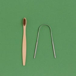 Toothbrush and tongue scraper on a green background. Zero waste concept.