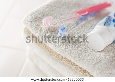 Toothbrush and towels on white tile