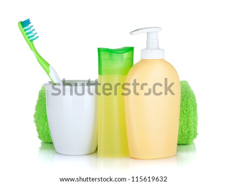 Toothbrush, cosmetics bottles and towel. Isolated on white background