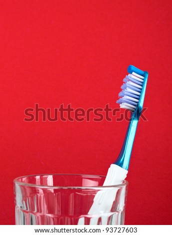 Toothbrush in transparent glass against red background