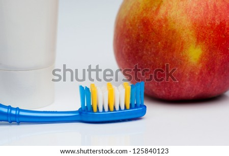 Toothbrush, toothpaste and apple
