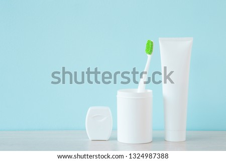 Toothbrush with green bristles in plastic glass, white tube of toothpaste and container of dental floss on shelf at pastel blue wall. Teeth hygiene. Empty place for text, quote, sayings or logo. Foto stock ©