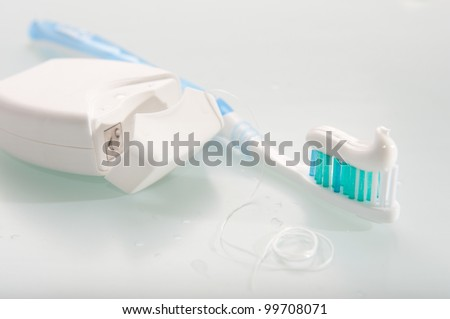 Toothbrush with toothpaste and dental floss on light background