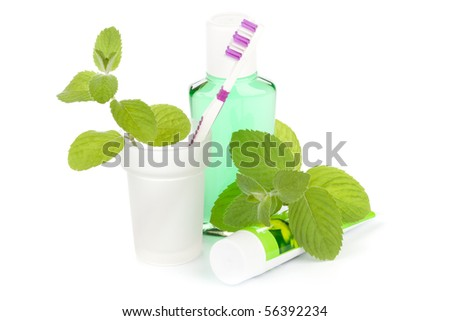 Toothbrush with toothpaste and fresh leaves of mint  on a white background.