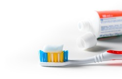 Toothbrush with toothpaste and tube of toothpaste over white background