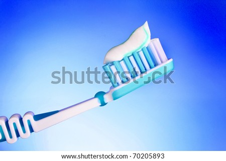 toothbrush with toothpaste on a blue background - stock photo