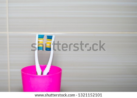 Toothbrushes in a plastic glass close-up. Copy space. Concept: hygiene, family relationships, intimate relationships, understanding, love