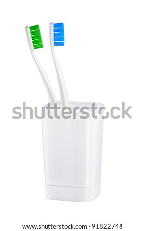toothbrushes in glass on a white background
