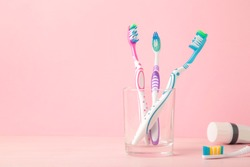 Toothbrushes in glass with tube of toothpaste on pink background. Top view