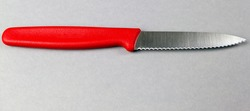 toothed kitchen knife on a gray background with space for a copy