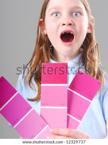 Toothless freckle faced girl excited holding pink paint sample chips