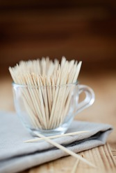 Toothpicks in a glass on a wooden table