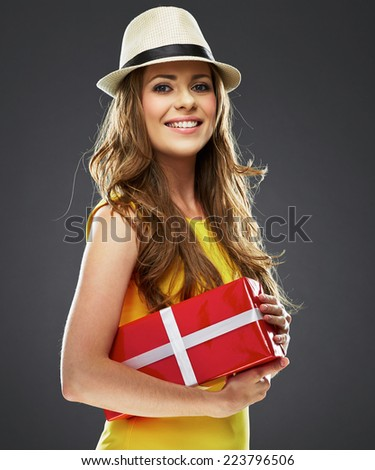 toothy smiling beautiful girl holding red present box . studio portrait of young woman with long hair.