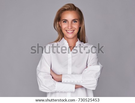 toothy smiling young pretty woman witn arms crossed. Beautiful girl isolated on grey