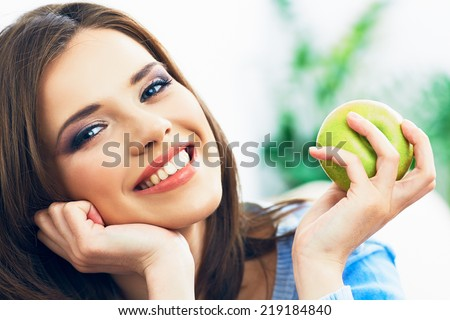Toothy smiling young woman close up face portrait with green apple.