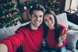 Top above angle photo of two people romantic guy and lady make v-signs selfie have christmas vacation x-mas holidays sit on divan in  house with newyear decoration illlumination indoors