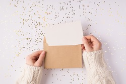 Top above close up overhead view photo of female hands holding kraft paper envelope with mock up copy space card inside over shiny golden background table