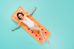Top above high angle full size photo of positive girl enjoy recreation resort swim lay inflatable orange mattress ocean wear style trendy body suit isolated over turquoise color background