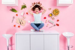 Top above high angle full size photo surprised girl culinary geek nerd sit table hold cookbook head prepare tasty pizza breakfast flat lay tomato utensils isolated pastel color background