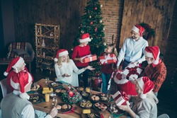 Top above high angle photo of big large family with small little kids mature sit around table x-mas meal man hold red sack back give gift box wish dream in house with christmas tree follow tradition