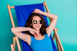 Top above high angle photo of positive girl enjoy summer travel trip sun bathing lie in comfort deckchair wear blue swimsuit isolated over teal color background