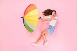 Top above high angle view full length photo of astonished crazy girl impressed parasol fly air wind blow cyclone lay scream wear white outfit isolated over pastel color background