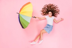 Top above high angle view full size profile side photo of positive girl lay hold umbrella fly air wind blow demonstrate empty space wear stylish clothes isolated over pastel color background