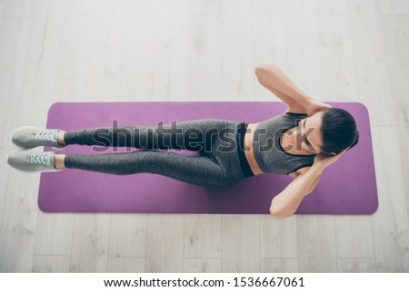Top above high angle view photo of cheerful positive sport girlfriend wearing sportswear doing crunches indoors on carpet floor