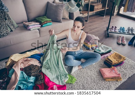 Top above high angle view photo of focused volunteer girl sit floor, carpet arrange her used clothes decide what she will give charity in house indoors Photo stock ©
