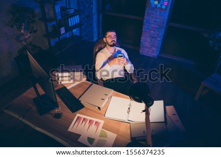 Top above high angle view photo of pensive thoughtful dreamy man looking pensively after having done his work in wait of shift over with hourglass on table