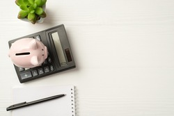 Top above overhead close up view photo of calculator with pink piggybank succulent spiral notepad isolated white wooden backdrop