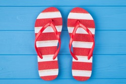 Top above overhead view close-up photo of a pair of red and white striped flipflops in center isolated on blue wooden background