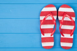 Top above overhead view close-up photo of a pair of striped flipflops placed to the right side isolated on blue wooden background with copyspace