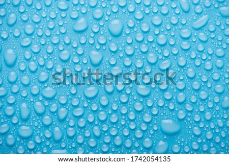 Top above overhead view close up photo of bright water drops on the blue background