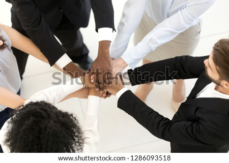 Top above overhead view diverse multiracial business people standing putting their hands together starting common business feels happy and excited. Teamwork, reliable person and togetherness concept